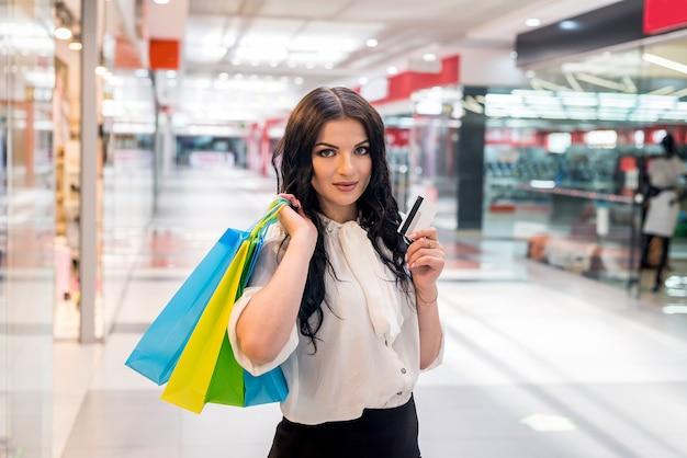 Dziewczyna w centrum handlowym z paczkami i kartą bankową