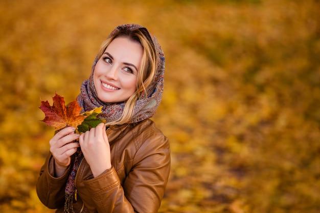 Dziewczyna w chustce na głowie chodzi po jesiennym parku