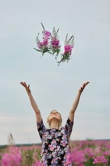 Dziewczyna w ciąży spaceru w polu kwiatów fireweed, uśmiechnięta kobieta i zbieranie kwiatów. dziewczynka spodziewa się narodzin dziecka