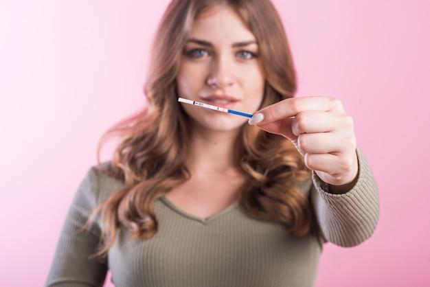 Dziewczyna w ciąży trzyma test ciążowy z wynikiem pozytywnym w ręku w studio na różowym tle