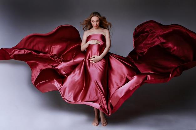 Dziewczyna w ciąży w czerwonej sukience piękna tekstura tkaniny na jasnym tle