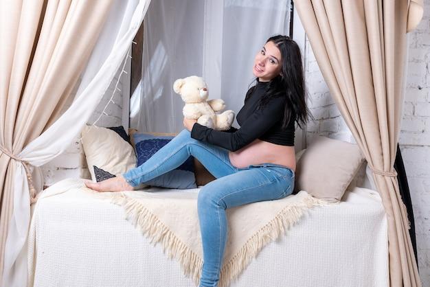 Dziewczyna w ciąży w niebieskie dżinsy i górę. zdjęcie wysokiej jakości