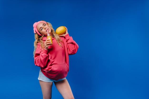 Dziewczyna w ciąży w różowe ubrania z butelką soku i melona na niebieskim tle.