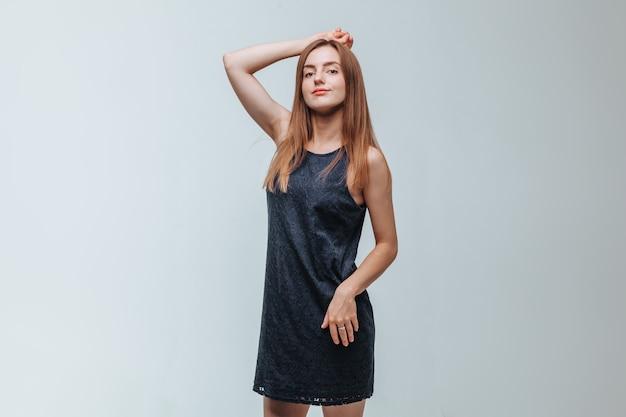 Dziewczyna w ciemnej sukience pozuje na szarym tle