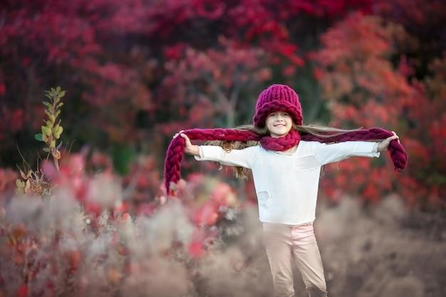 Dziewczyna w ciepłej dzianej wełnianej czapce i czerwonym szaliku na tle jesiennego lasu