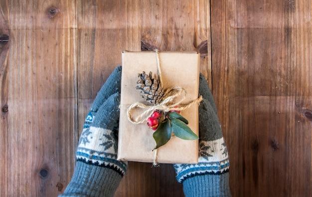 Dziewczyna w ciepłych rękawiczkach trzyma świąteczny prezent w rustykalnym stylu
