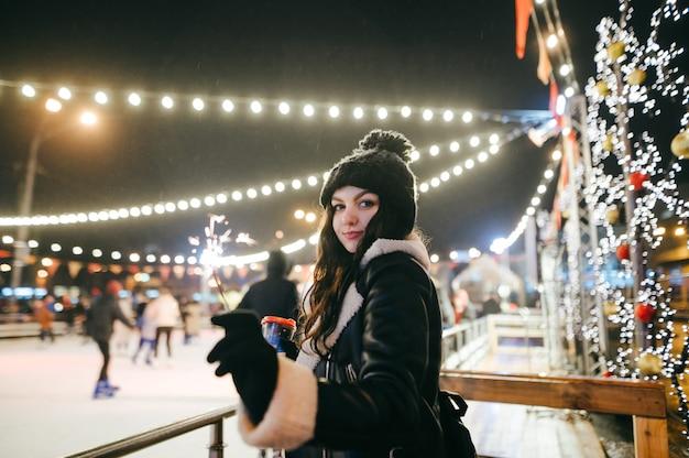 Dziewczyna w ciepłych ubraniach na lodowisku