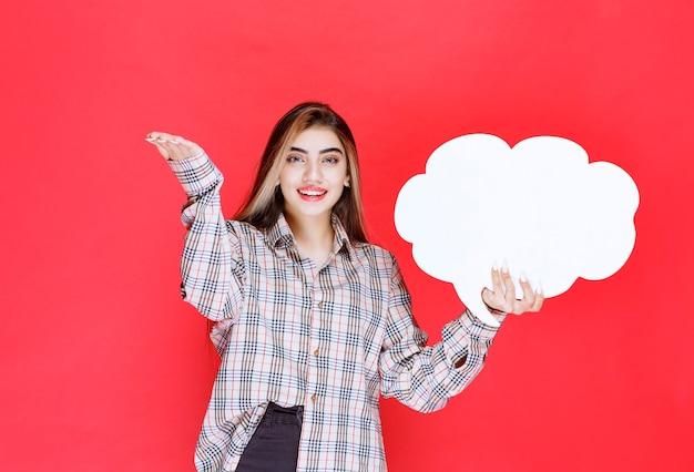 Dziewczyna w ciepłym swetrze trzymająca tablicę z pomysłami w kształcie chmurki i wskazująca osobę z przodu