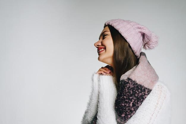 Dziewczyna w ciepłym ubraniu uśmiecha się ze wzruszenia i spleciła ręce w pobliżu twarzy
