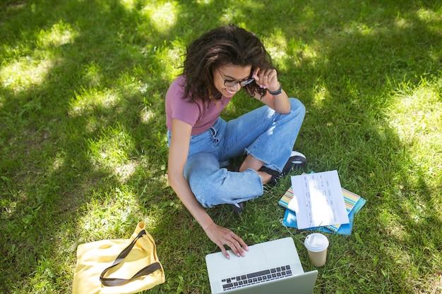 Dziewczyna w codziennych ubraniach siedzi na trawie w parku i studiuje