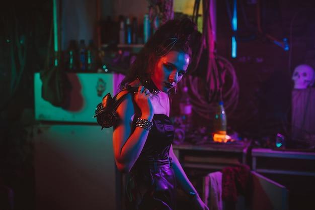 Dziewczyna w cyberpunkowym garniturze z neonowym światłem w garażu. steampunkowy cosplay w stylu postapokaliptycznym