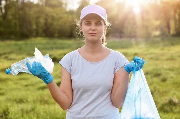 Dziewczyna w czapce baseballowej, białej koszulce i niebieskich lateksowych rękawiczkach, trzyma worek na śmieci pełen śmieci, pani wygląda na zmęczoną, czyści brudną łąkę, zbiera śmieci. problemy ekologiczne.