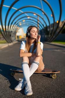 Dziewczyna w czapce baseballowej siedzi na deskorolce, longboard. latem w mieście przy asfaltowej drodze młoda kobieta. w ręku smartfon, aplikacja do internetu. wolne miejsce na tekst
