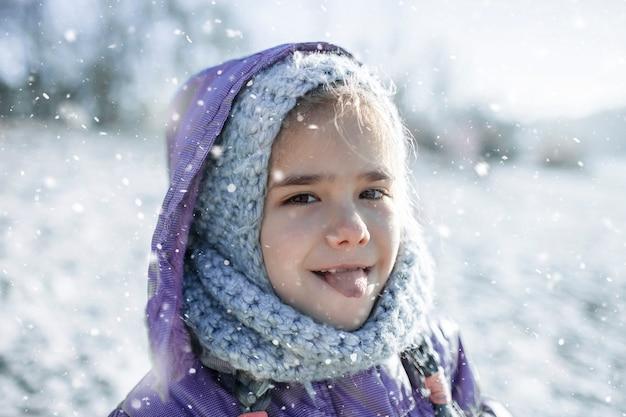 Dziewczyna w czapce, ciesząc się pierwszym zimowym śniegiem i degustując go z językiem