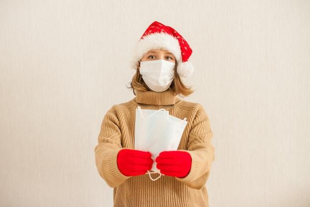 Dziewczyna w czapce mikołaja i medycznej masce ochronnej trzyma maskę w dłoniach. nowy rok 2021