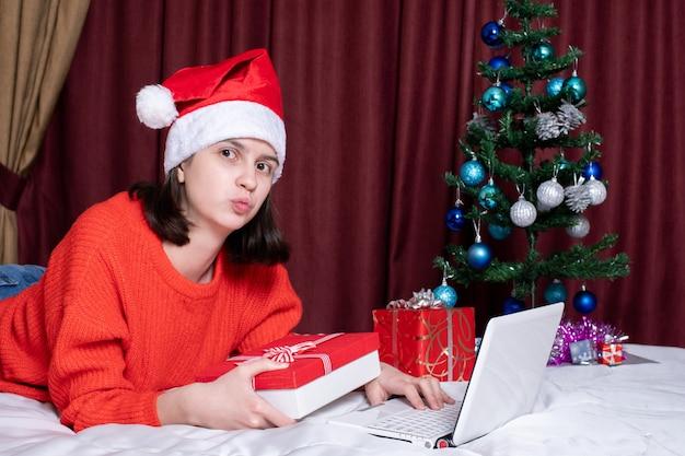 Dziewczyna w czapce świętego mikołaja i czerwonym swetrze z dzianiny przekazuje buziaka na prezenty lub zakupy. koncepcja na życzenia świąteczne podczas samoizolacji. świąteczne zakupy i prezenty