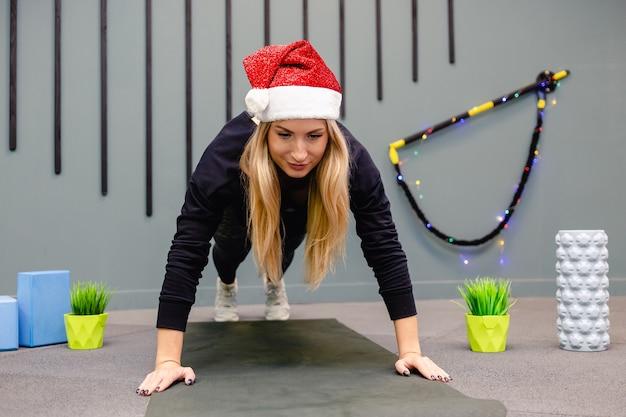 Dziewczyna w czapce świętego mikołaja robi ćwiczenia fitness na siłowni