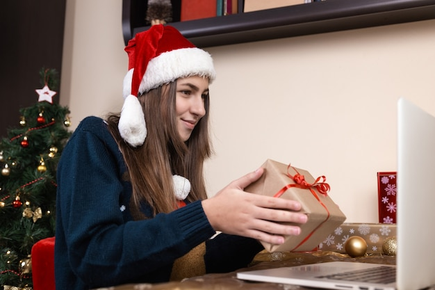 Dziewczyna w czapce świętego mikołaja rozmawia i daje prezent za pomocą laptopa dla przyjaciół i rodziców połączeń wideo. pokój jest odświętnie urządzony. boże narodzenie w okresie koronawirusa.