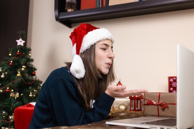 Dziewczyna w czapce świętego mikołaja rozmawia za pomocą laptopa do przyjaciół i rodziców połączeń wideo. pokój jest odświętnie urządzony. boże narodzenie w okresie koronawirusa. pocałunek w powietrzu