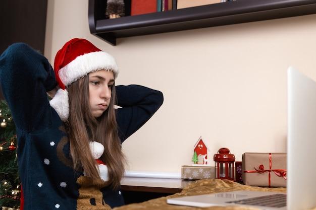 Dziewczyna w czapce świętego mikołaja rozmawia za pomocą laptopa do przyjaciół i rodziców połączeń wideo. pokój jest odświętnie urządzony. boże narodzenie w okresie koronawirusa. zmęczenie