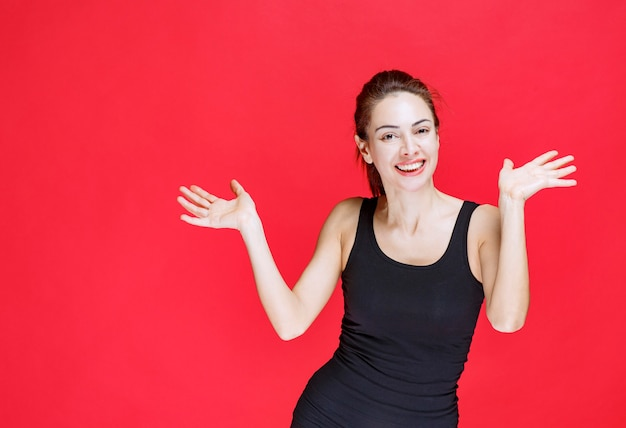 Dziewczyna w czarnej koszuli czuje się pozytywnie i delikatnie się uśmiecha. zdjęcie wysokiej jakości