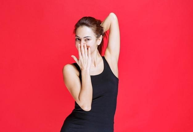 Dziewczyna w czarnej koszuli dająca uwodzicielskie i atrakcyjne pozy. zdjęcie wysokiej jakości