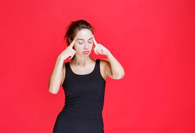 Dziewczyna w czarnej koszuli jest zmęczona i śpiąca. zdjęcie wysokiej jakości