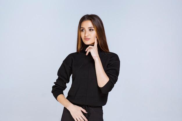 Dziewczyna w czarnej koszuli myśli i analizuje. zdjęcie wysokiej jakości