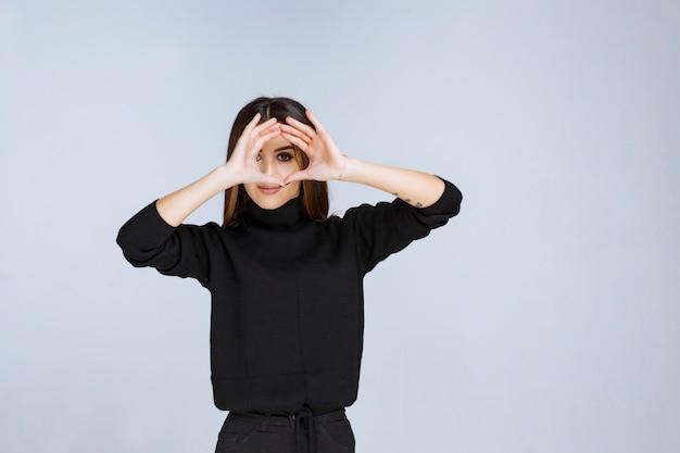 Dziewczyna w czarnej koszuli patrząc przez palce. zdjęcie wysokiej jakości