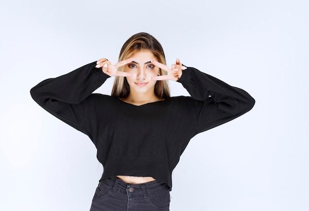 Dziewczyna w czarnej koszuli patrząc przez palce.