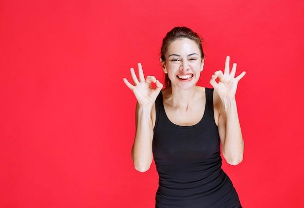 Dziewczyna w czarnej koszuli pokazano pozytywny znak ręką. zdjęcie wysokiej jakości