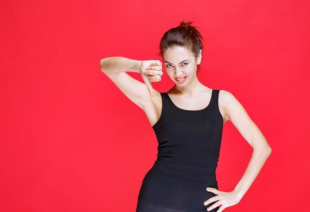 Dziewczyna w czarnej koszuli pokazując kciuk w dół znak. zdjęcie wysokiej jakości