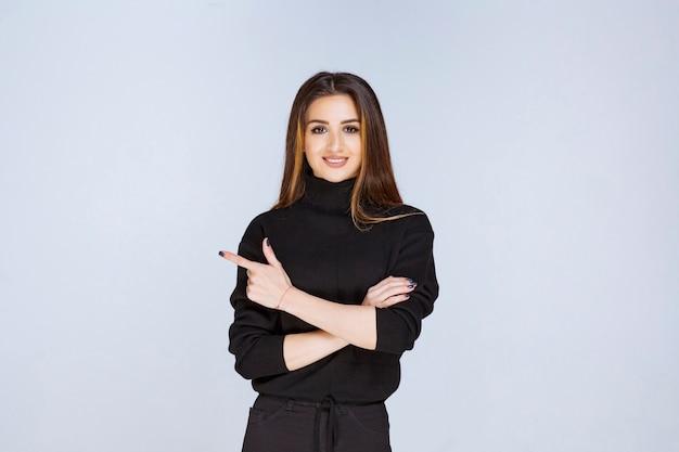 Dziewczyna w czarnej koszuli pokazując lewą stronę. zdjęcie wysokiej jakości