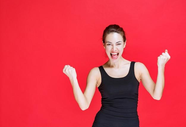 Dziewczyna w czarnej koszuli pokazując pięści i czując się szczęśliwa. zdjęcie wysokiej jakości