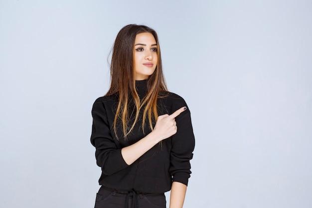 Dziewczyna w czarnej koszuli skierowana w prawo. zdjęcie wysokiej jakości
