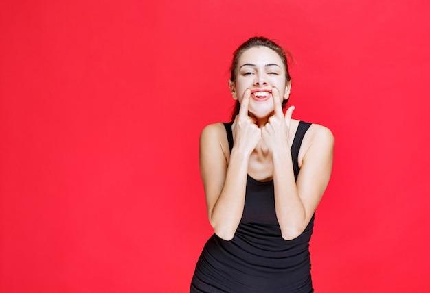 Dziewczyna w czarnej koszuli śmiejąca się głośno jak głupiec. zdjęcie wysokiej jakości