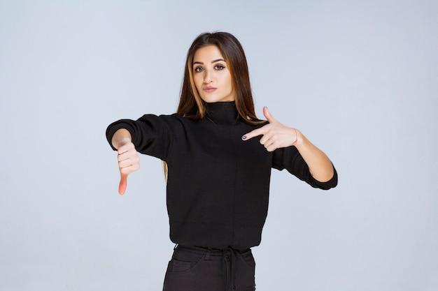 Dziewczyna w czarnej koszuli sprawdza jej czas. zdjęcie wysokiej jakości