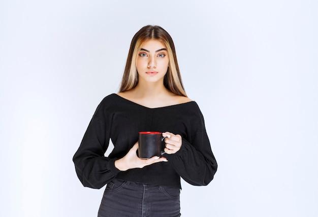 Dziewczyna w czarnej koszuli trzyma kubek czarnej kawy. zdjęcie wysokiej jakości