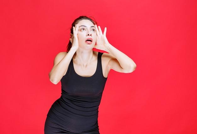 Dziewczyna w czarnej koszuli trzymająca głowę i reagująca jak głupiec. zdjęcie wysokiej jakości