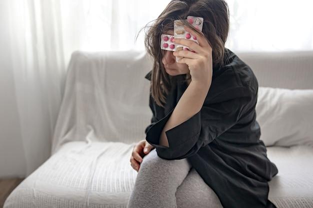 Dziewczyna w czarnej koszuli w domu cierpi na ból psychiczny lub fizyczny, trzyma w rękach tabletki.