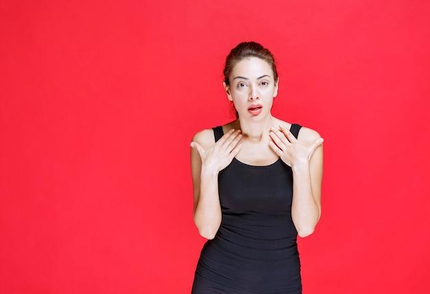 Dziewczyna w czarnej koszuli, wskazując na siebie. zdjęcie wysokiej jakości