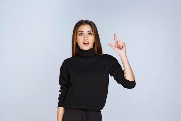 Dziewczyna w czarnej koszuli, wskazując powyżej. zdjęcie wysokiej jakości