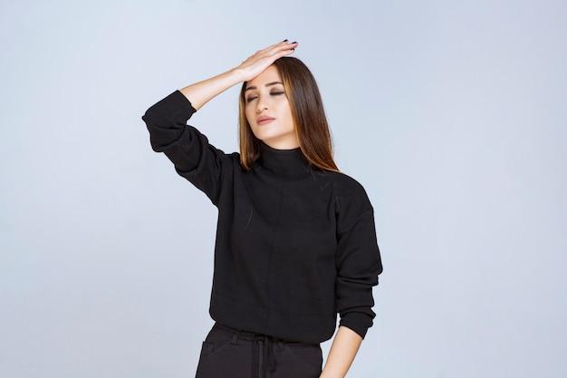 Dziewczyna w czarnej koszuli wygląda na wyczerpaną i senną. zdjęcie wysokiej jakości