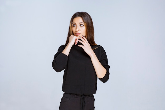 Dziewczyna w czarnej koszuli wygląda zamyślona. zdjęcie wysokiej jakości