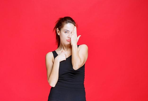 Dziewczyna w czarnej koszuli zasłaniając jedno oko i patrząc innym. zdjęcie wysokiej jakości