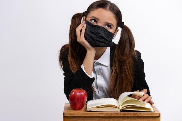 Dziewczyna w czarnej masce siedzi przy stole z książką i białą ścianą jabłka