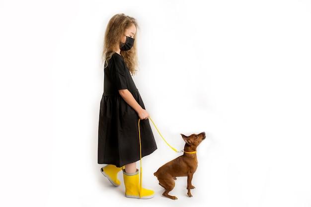 Dziewczyna w czarnej ochronnej masce przeciwwirusowej spaceruje z psem. nowa rzeczywistość podczas pandemii covid-19. środki ostrożności w przypadku pandemii koronawirusa. podróżowanie ze zwierzętami. zdjęcie wysokiej jakości