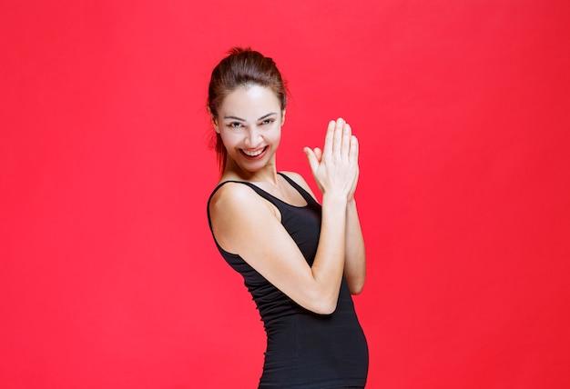 Dziewczyna w czarnej sportowej koszuli brawo występ. zdjęcie wysokiej jakości