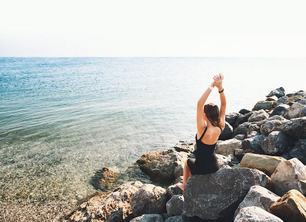 Dziewczyna w czarnej sukience na tle morza lub jeziora kobieta zrelaksowana nad morzem na dużej dzikiej kamiennej plaży
