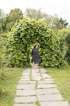 Dziewczyna w czarnej sukience vintage biegnie w zielonym labiryncie, wiosenny nastrój. wysokiej jakości zdjęcie